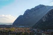 Riva del Garda városa háttérben a Garda-tóval. A párás, őszi levegőben a délutáni napfény átszűrődik a környező hegyek között.
